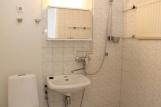 Vaalea kylpyhuone; osin laatta, harmaa muovimatto