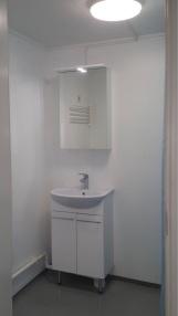 Kylpyhuoneessa uusi allaskaappi, peilikaappi ja valaistus