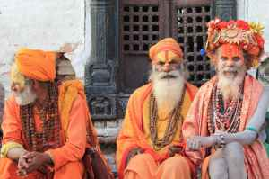 three men wearing orange tradition clothes